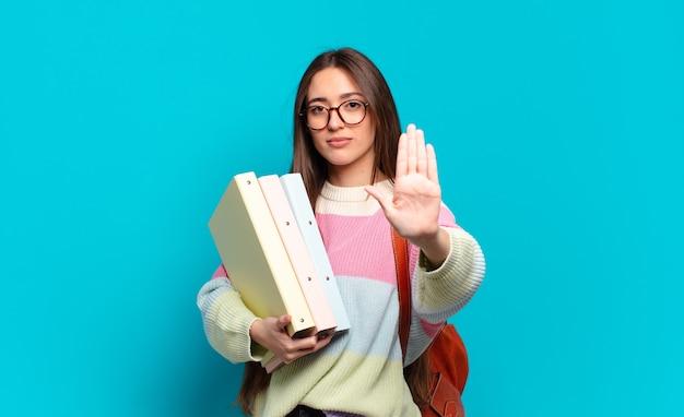 Mujer bonita joven que parece seria, severa, disgustada y enojada mostrando la palma abierta haciendo gesto de parada.