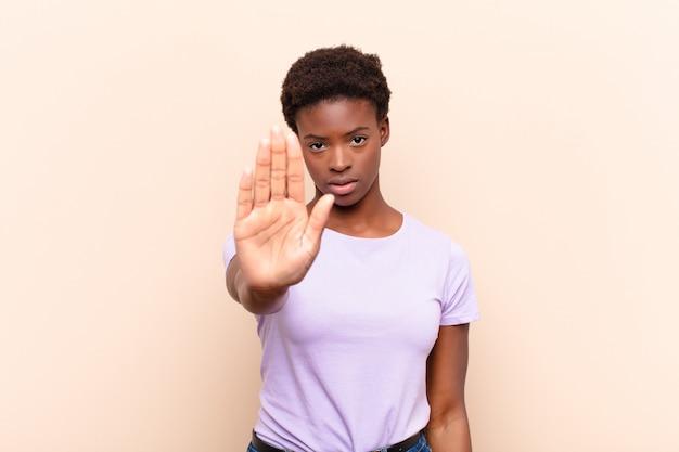 Mujer bonita joven que parece seria, severa, disgustada y enojada mostrando la palma abierta haciendo gesto de parada
