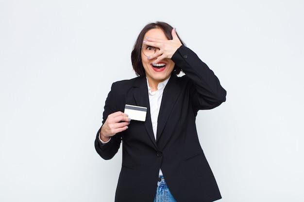Mujer bonita joven que parece sorprendida, asustada o aterrorizada, cubriéndose la cara con la mano y mirando entre los dedos con una tarjeta de crédito