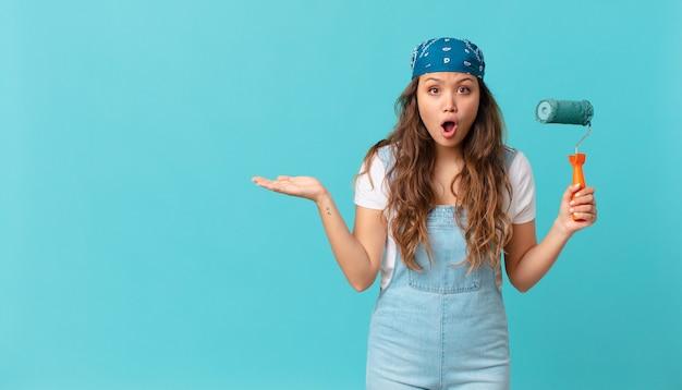 Mujer bonita joven que parece sorprendida y conmocionada, con la mandíbula caída sosteniendo un objeto y pintando una pared