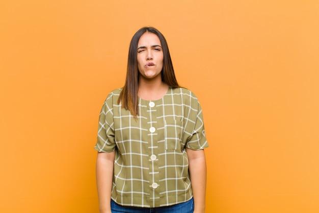 Mujer bonita joven que parece tonta y divertida con una expresión tonta con los ojos cruzados, bromeando y bromeando aislado contra la pared naranja