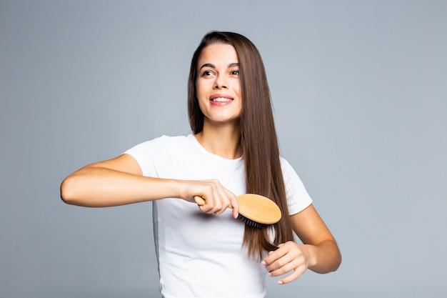 Mujer bonita joven que se peina el pelo aislado en blanco