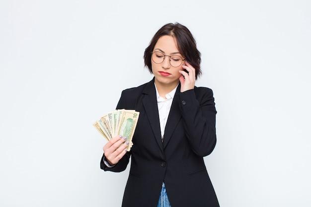 Mujer bonita joven que se siente aburrida, frustrada y con sueño después de una tarea aburrida, aburrida y tediosa, sosteniendo la cara con la mano con billetes