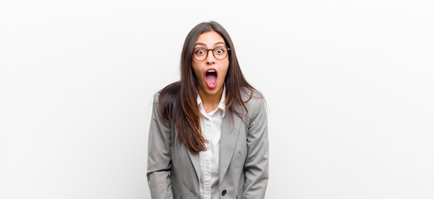 Mujer bonita joven que se siente aterrorizada y conmocionada, con la boca abierta de sorpresa en la pared blanca aislada