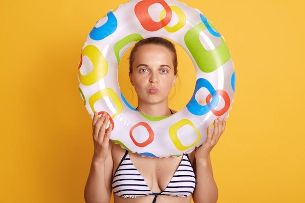 La mujer bonita joven que se siente cansada y frustrada, que parece frustrada con el problema, que presenta con los labios fruncidos, que sostiene el anillo inflable delante de la cara, se coloca contra la pared amarilla.