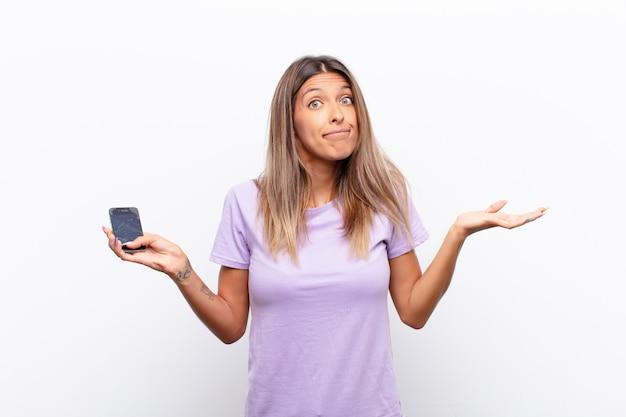 Mujer bonita joven que se siente confundida y confundida, dudando, sopesando o eligiendo diferentes opciones con expresión divertida sosteniendo un teléfono inteligente