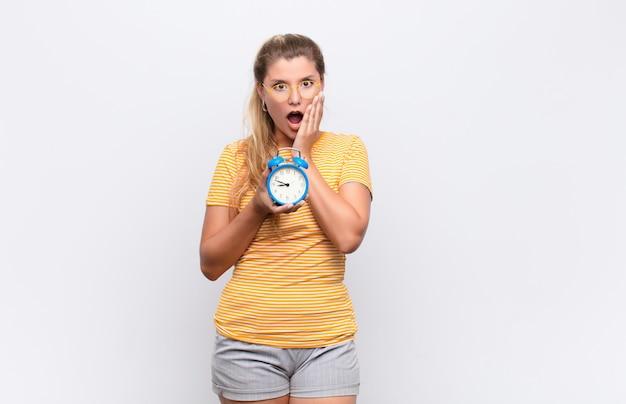 Mujer bonita joven que se siente conmocionada y asustada, mirando aterrorizada con la boca abierta y las manos en las mejillas con un reloj despertador