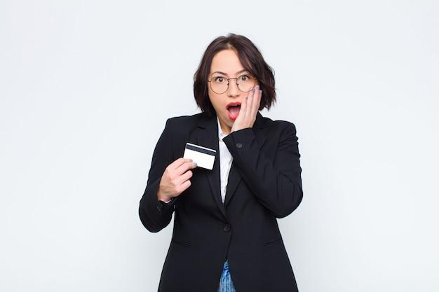 Mujer bonita joven que se siente conmocionada y asustada, se ve aterrorizada con la boca abierta y las manos en las mejillas con una tarjeta de crédito