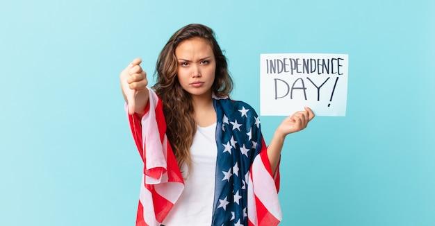 Mujer bonita joven que se siente cruzada, mostrando los pulgares hacia abajo el concepto del día de la independencia