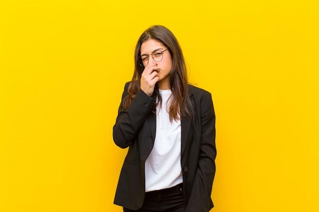 Mujer bonita joven que se siente disgustada, tapándose la nariz para evitar oler un hedor desagradable y desagradable contra la pared naranja