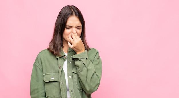 Mujer bonita joven que se siente disgustada, tapándose la nariz para evitar oler un hedor desagradable y desagradable