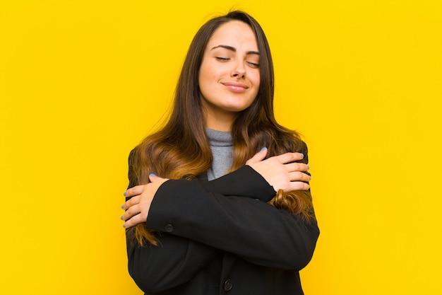Mujer bonita joven que se siente enamorada, sonriendo, abrazándose y abrazándose a sí misma, manteniéndose soltera, siendo egoísta y egocéntrica, concepto de trabajo o negocio