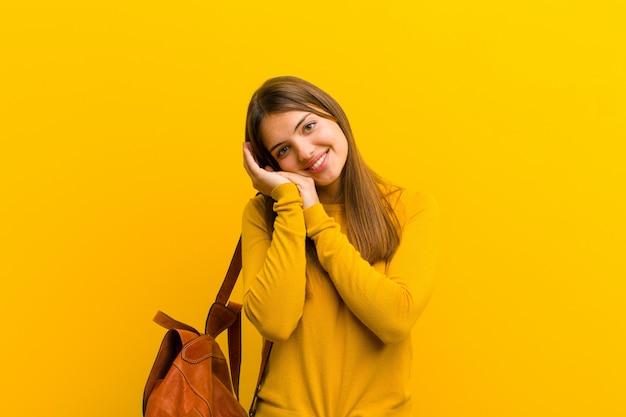 Mujer bonita joven que se siente enamorada y se ve linda, adorable y feliz, sonriendo románticamente con las manos junto a la cara contra la pared naranja