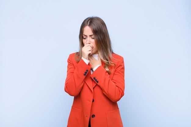 Mujer bonita joven que se siente enferma con dolor de garganta y síntomas de gripe, tos con la boca cubierta sobre una pared azul