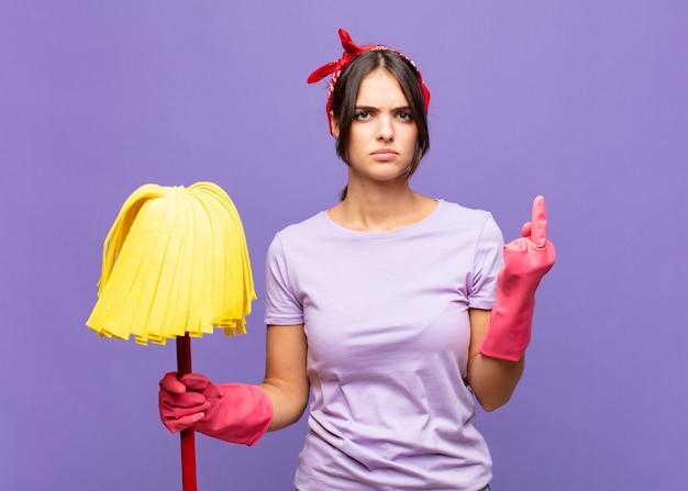 Mujer bonita joven que se siente enojada, molesta, rebelde y agresiva, moviendo el dedo medio, contraatacando