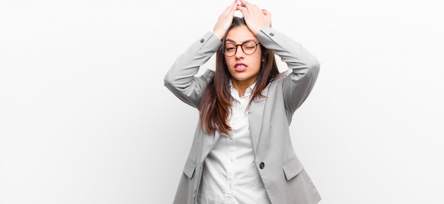 Mujer bonita joven que se siente estresada y ansiosa, deprimida y frustrada con dolor de cabeza, levantando ambas manos contra la pared blanca