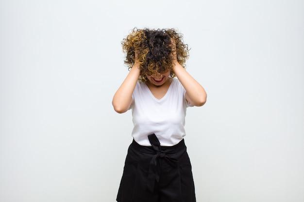 Mujer bonita joven que se siente estresada y frustrada, levantando las manos a la cabeza, sintiéndose cansada, infeliz y con migraña contra la pared blanca