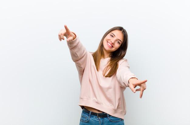 Mujer bonita joven que se siente feliz y confiada, apuntando a la cámara con ambas manos y riendo, eligiéndote sobre una pared blanca
