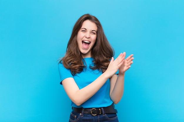 Mujer bonita joven que se siente feliz y exitosa, sonriendo y aplaudiendo, saludando con un aplauso contra la pared azul