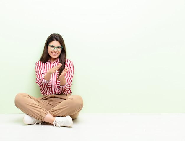 Mujer bonita joven que se siente feliz y exitosa, sonriendo y aplaudiendo, saludando con un aplauso sentado en el suelo