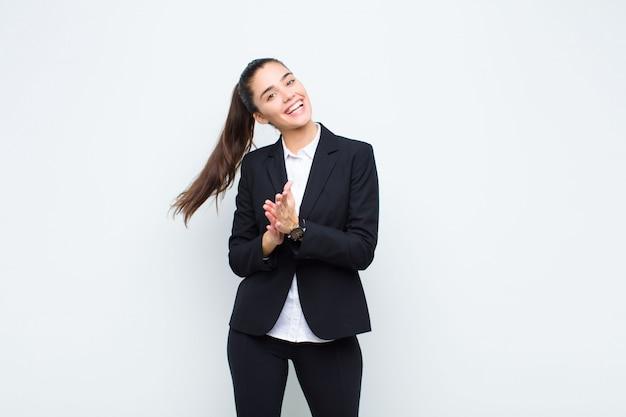 Mujer bonita joven que se siente feliz y exitosa, sonriendo y aplaudiendo, saludando con un concepto de negocio de aplausos