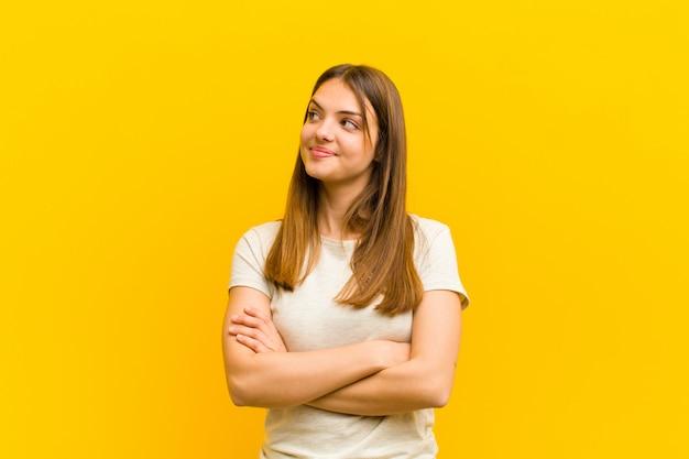 Mujer bonita joven que se siente feliz, orgullosa y esperanzada, preguntándose o pensando, mirando hacia arriba para copiar el espacio con los brazos cruzados sobre fondo naranja