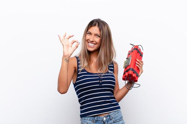 Mujer bonita joven que se siente feliz, relajada y satisfecha, mostrando aprobación con gesto bien, sonriendo con una bomba de dinamita