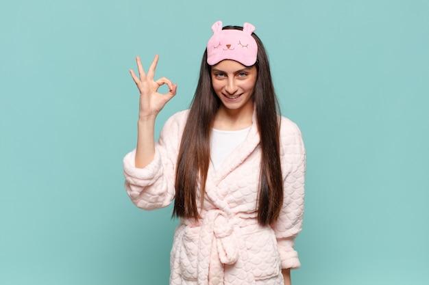 Mujer bonita joven que se siente feliz, relajada y satisfecha, mostrando aprobación con gesto bien, sonriendo. despertar vistiendo concepto de pijama