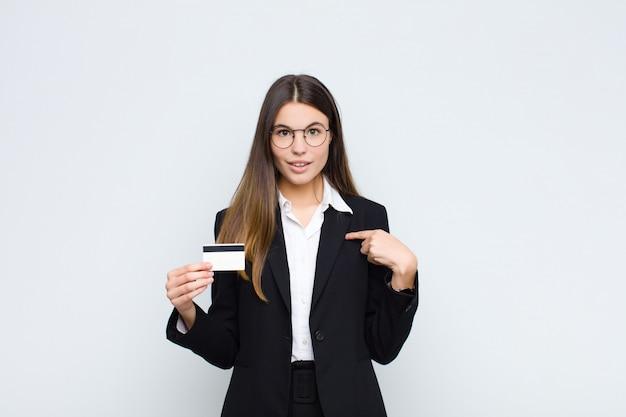 Mujer bonita joven que se siente feliz, sorprendida y orgullosa, apuntando a sí misma con una mirada emocionada y asombrada con una tarjeta de crédito