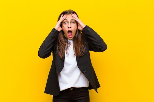 Mujer bonita joven que se siente horrorizada y conmocionada, levantando las manos a la cabeza y entrando en pánico ante un error contra la pared naranja