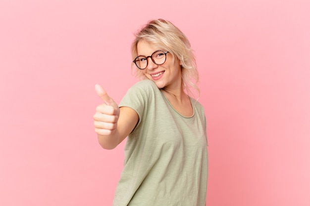 Mujer bonita joven que se siente orgullosa, sonriendo positivamente con los pulgares hacia arriba