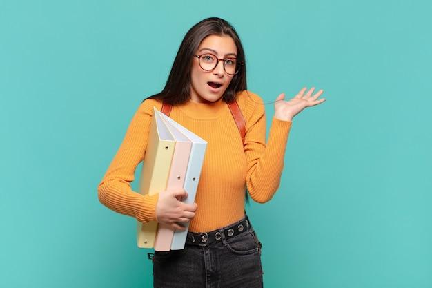 Mujer bonita joven que se siente perpleja y confundida, dudando, ponderando o eligiendo diferentes opciones con expresión divertida. concepto de estudiante