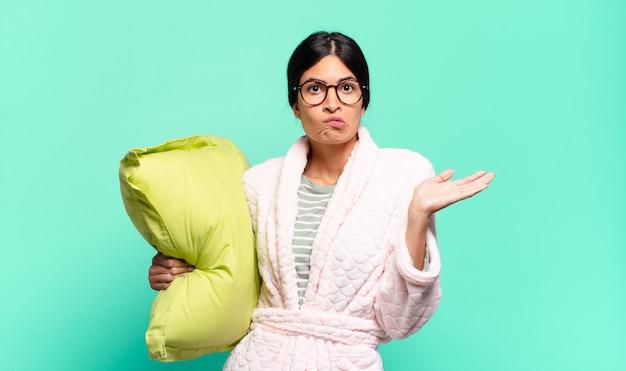 Mujer bonita joven que se siente perpleja y confundida, dudando, ponderando o eligiendo diferentes opciones con expresión divertida. concepto de pijama