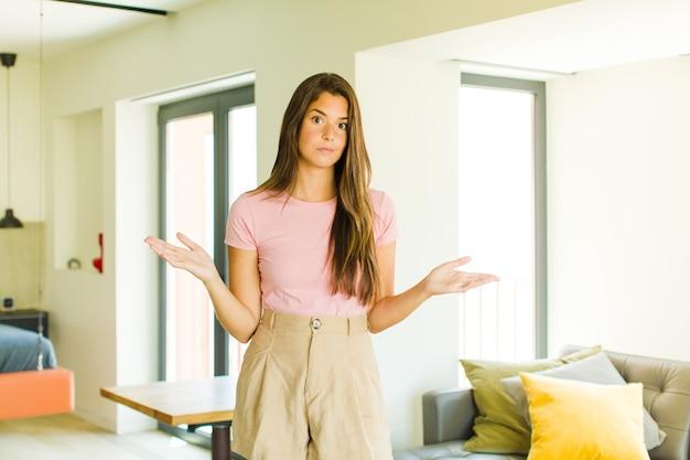 Mujer bonita joven que se siente perpleja y confundida, insegura de la respuesta o decisión correcta, tratando de tomar una decisión
