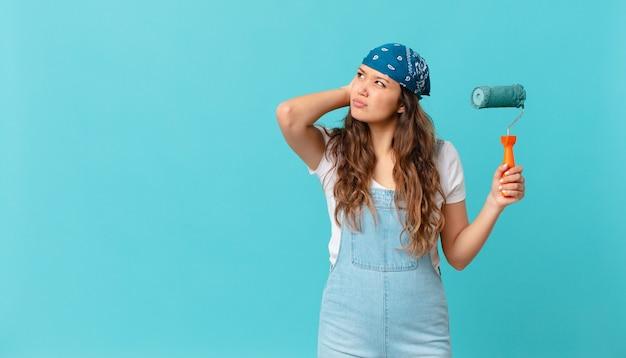 Mujer bonita joven que se siente perpleja y confundida, rascándose la cabeza y pintando una pared