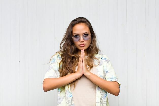 Mujer bonita joven que se siente preocupada, esperanzada y religiosa, orando fielmente con las palmas presionadas, pidiendo perdón