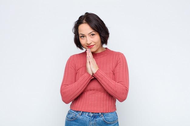 Mujer bonita joven que se siente preocupada, esperanzada y religiosa, rezando fielmente con las palmas presionadas, pidiendo perdón contra la pared blanca