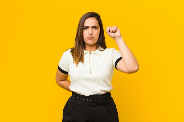 Mujer bonita joven que se siente seria, fuerte y rebelde, levantando el puño, protestando o luchando por la revolución aislada contra la pared naranja