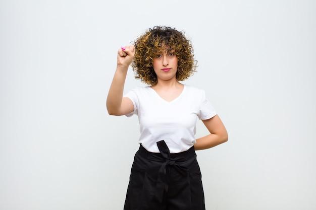 Mujer bonita joven que se siente seria, fuerte y rebelde, levantando el puño, protestando o luchando por la revolución contra la pared blanca