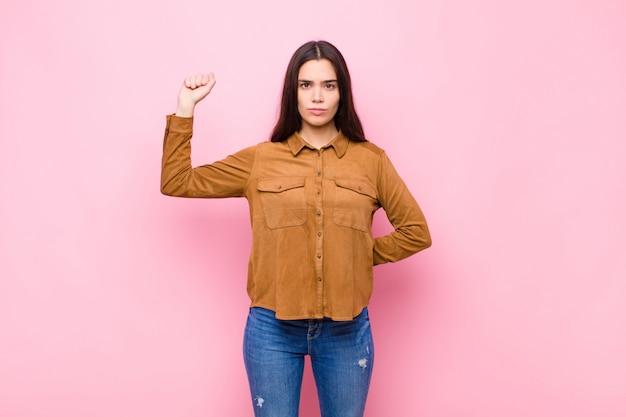 Mujer bonita joven que se siente seria, fuerte y rebelde, levantando el puño, protestando o luchando por la revolución contra la pared rosa
