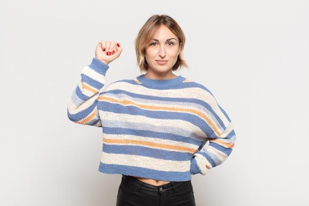 Mujer bonita joven que se siente seria, fuerte y rebelde, levantando el puño, protestando o luchando por la revolución