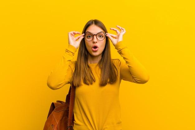 Mujer bonita joven que se siente sorprendida, asombrada y sorprendida, sosteniendo gafas con una mirada asombrada e incrédula sobre fondo naranja