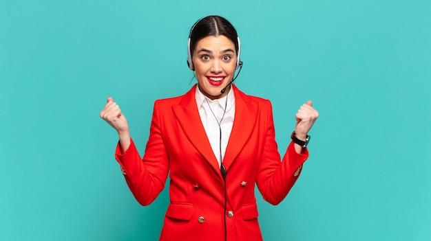 Mujer bonita joven que se siente sorprendida, emocionada y feliz, riendo y celebrando el éxito, diciendo ¡guau !. concepto de telemarketer
