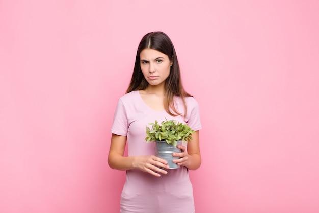 Mujer bonita joven que se siente triste y llorona con una mirada infeliz, llorando con una actitud negativa y frustrada con una planta