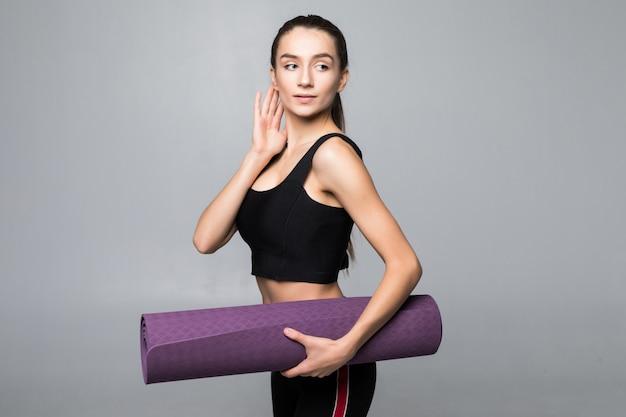 Mujer bonita joven que sostiene el colchón de yoga antes de ejercicios aislados en la pared gris
