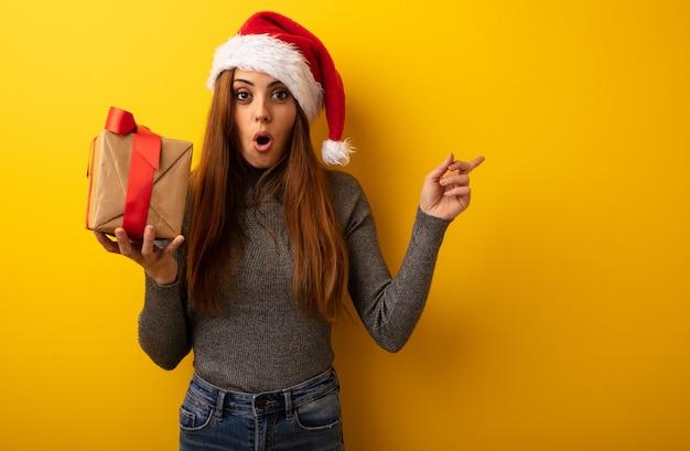 Mujer bonita joven que sostiene el regalo que señala al lado