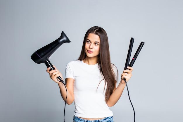 Mujer bonita joven que sostiene el secador de pelo y alisar aislado en blanco