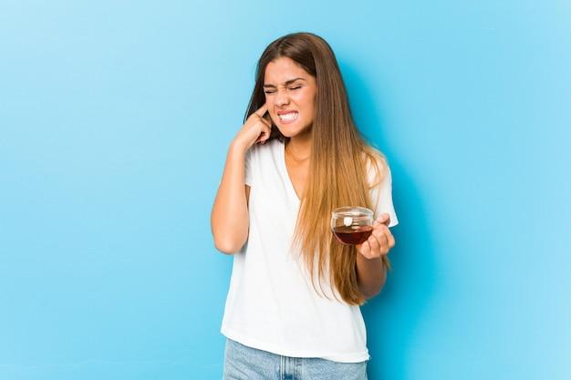 Mujer bonita joven que sostiene una taza de té que cubre los oídos con las manos.