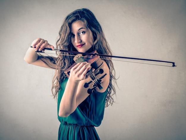 Mujer bonita joven que toca en un violín