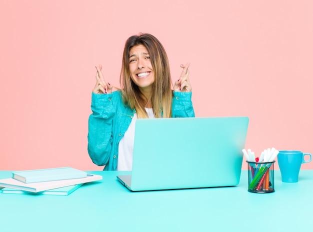 Mujer bonita joven que trabaja con una computadora portátil cruzando los dedos ansiosamente y esperando buena suerte con una mirada preocupada